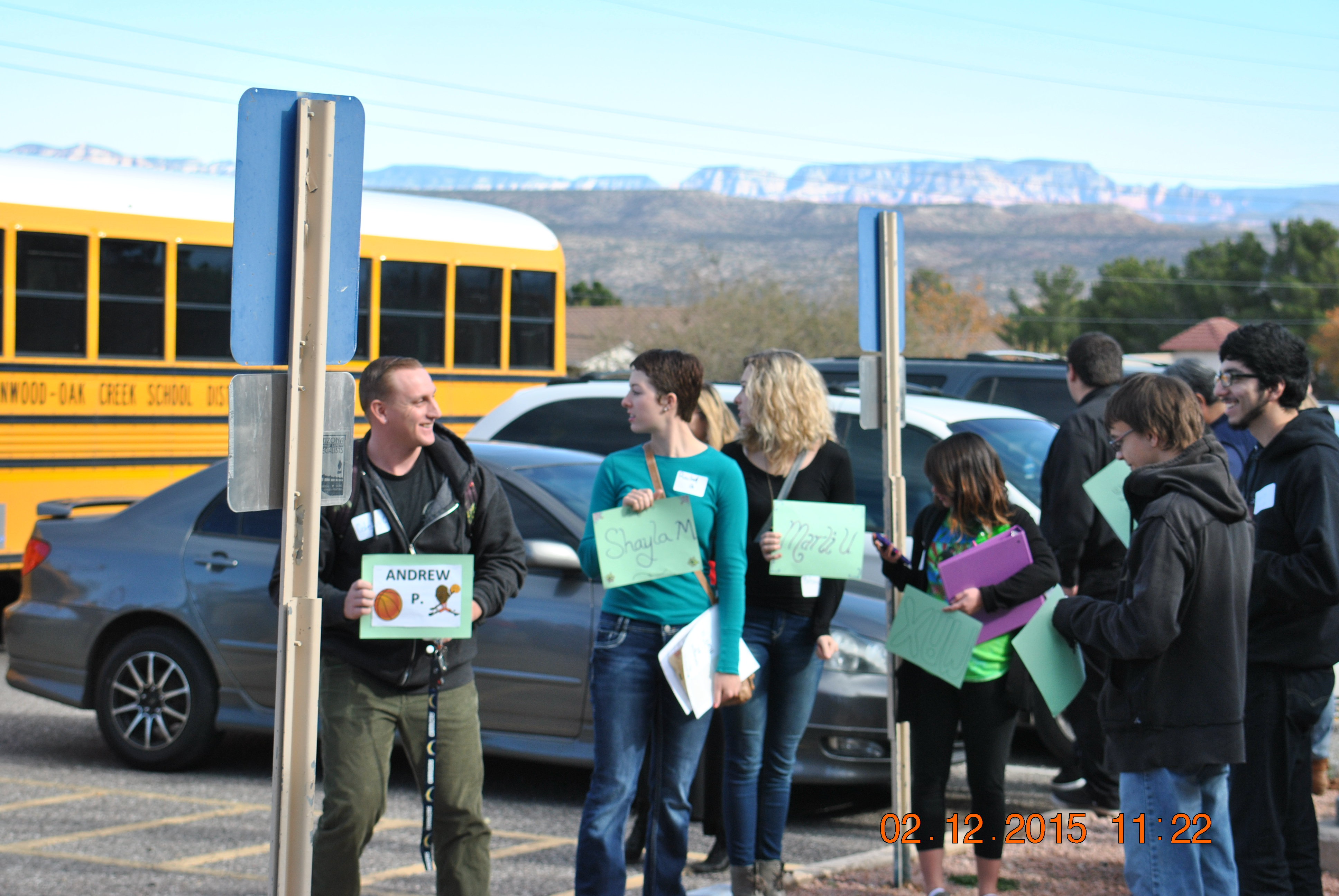Yavapai College students holding up signs of their pen pal's name, waiting outside for their pen pals to arrive.
